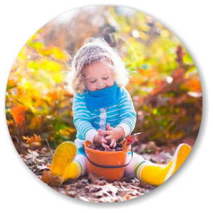 little girl sitting with leaves